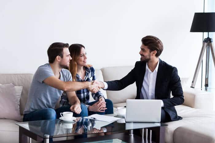 Ein Mann der Immobilien vermieten möchte und ein Paar, dass gerade den Mietvertrag unterzeichnet.