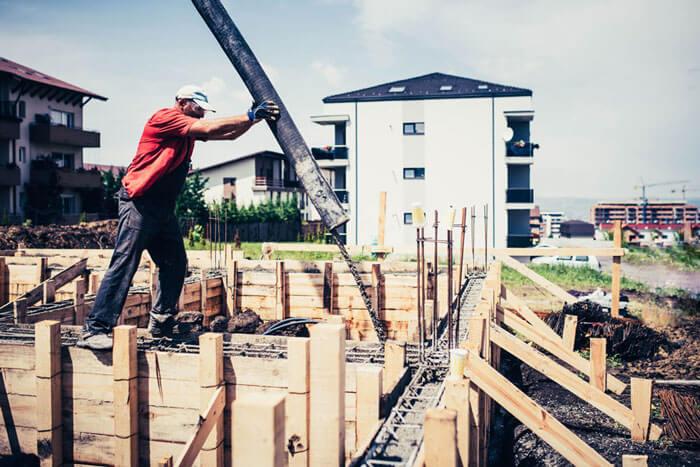 Bauarbeiter beim Aufschütten eines Fundaments