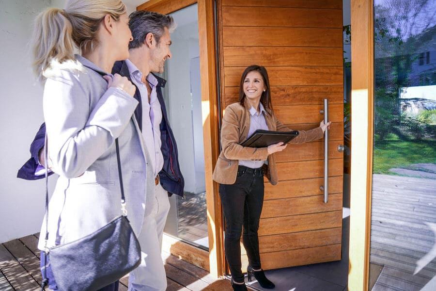 Eine Maklerin in der Eingangstür von einem Einfamilienhaus