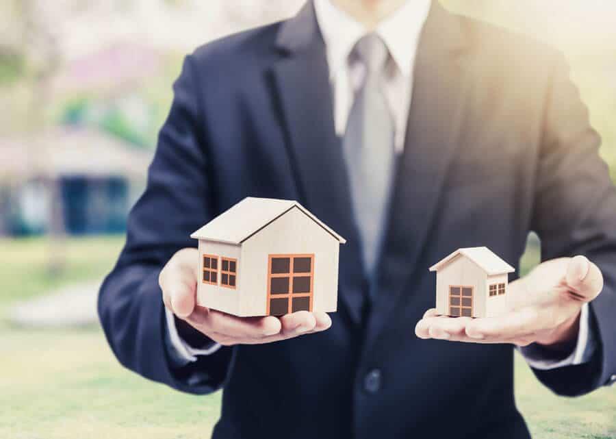Immobilien mieten – Welche Immobilie darf's sein? Ein Mann der zwei unterschiedlich große Modellhäuser in der Hand hält.