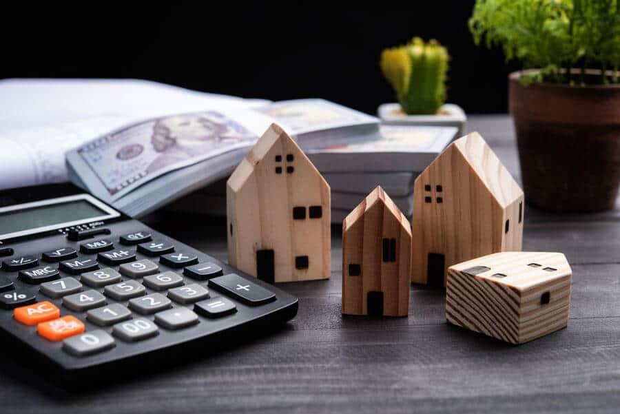 Ansicht eines Taschenrechners und Modellhäuser um die Immobilienpreise zu visualisieren