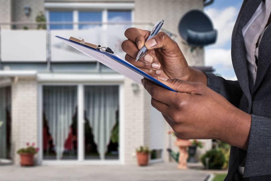 Eine Person die mit einem Klemmbrett vor einem Haus steht
