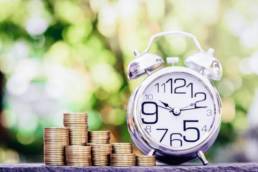 Eine Uhr im Freien, neben Geldstapeln