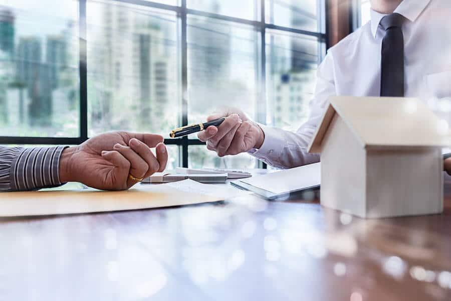 Zwei Personen, die Unterlagen zu Immobilien unterzeichnen