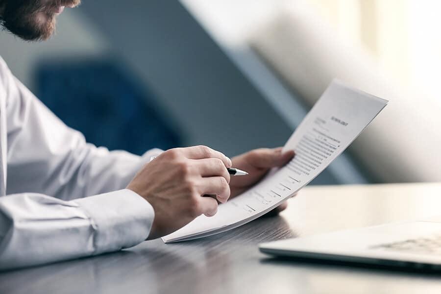 Schufa-Auskunft für Vermieter: Ein Mann am Schreibtisch mit Dokumenten