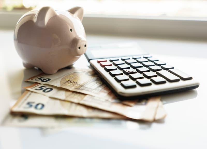 Ein Sparschwein mit Geld und Taschenrechner, beim Hauskauf lässt sich Geld sparen