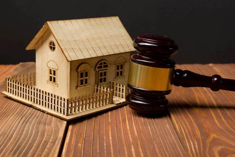 Ein Holzhaus und ein Hammer der Zwangsversteigerung