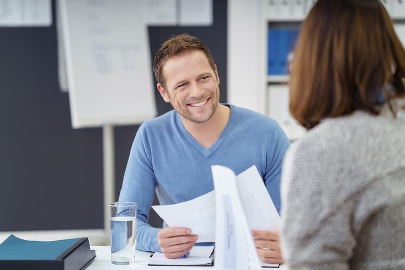 Ein Mann erhält seine Unbedenklichkeitsbescheinigung und lächelt