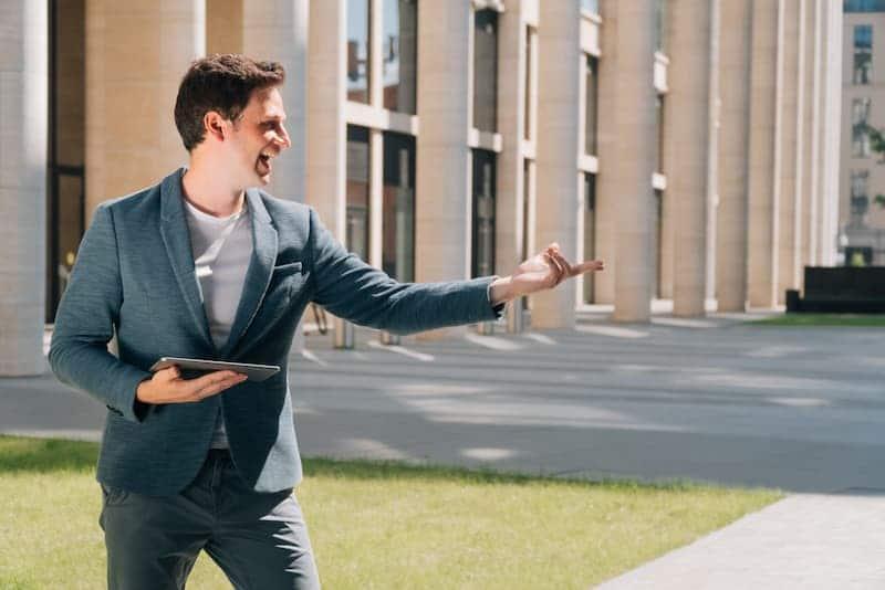 Ein junger Mann freut sich, er macht eine Immobilienmakler-Ausbildung