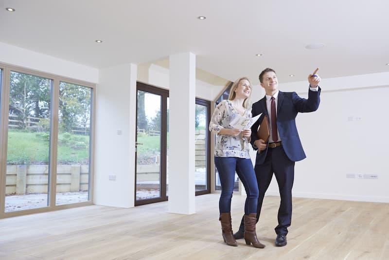 Ein Paar in einer leerstehenden Wohnung diskutiert: Wie kann man Immobilienmakler werden?