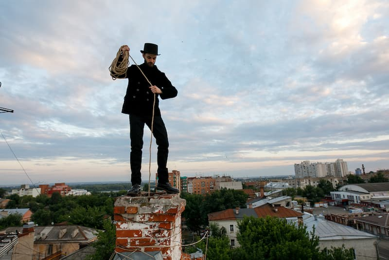 Ein Schornsteinfeger geht auf dem Dach seiner Arbeit nach, der Feuerstättenschau