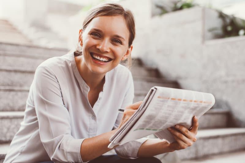 Eine Frau freut sich, da sie die Tricks von Betrügern bei Fakewohnungsanzeigen kennt