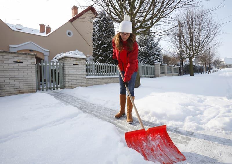 Eine Frau macht den Winterdienst und schippt den Schnee weg