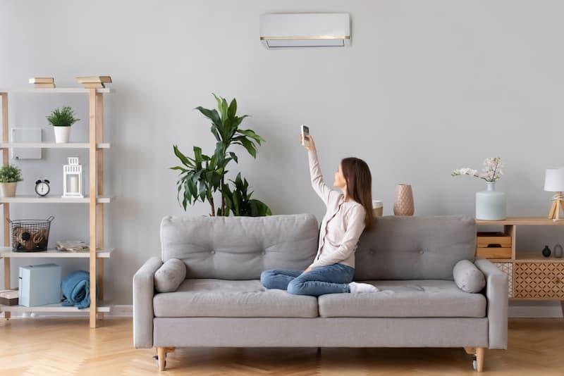 Eine Frau schaltet die Klimaanlage in der Wohnung ein