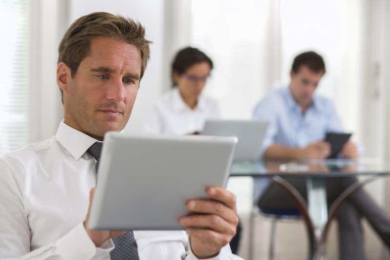 Ein Mann hält ein Tablet in der Hand, er ist auf einer Weiterbildung für Immobilienmakler