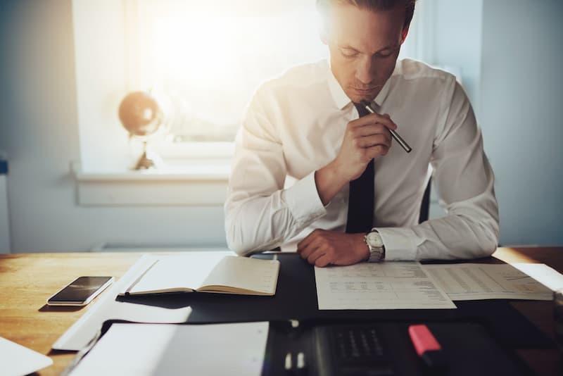 Ein Mann sitzt am Schreibtisch und möchte eine Immobilien GmbH gründen