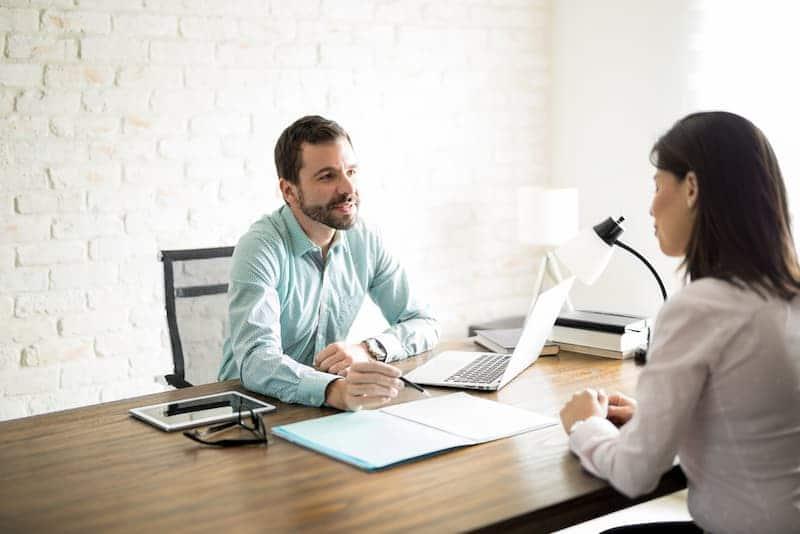 Ein Mann sitzt mit einer Frau am Tisch und erklärt die Bedingungen von einem Bauspardarlehen