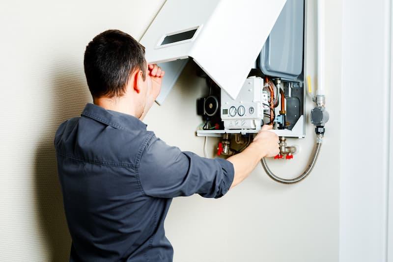 Ein Mann überprüft den Boiler einer Gasheizung