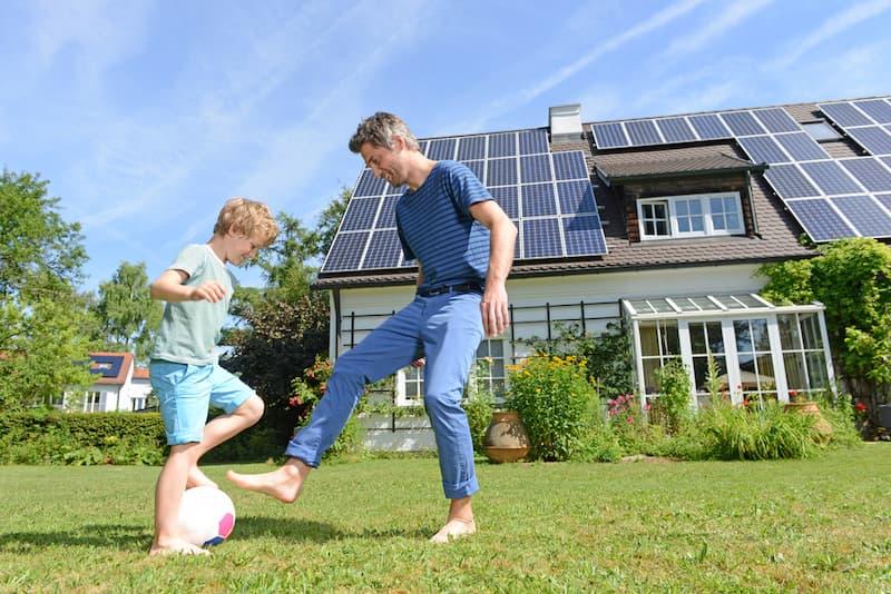 Ein Mann mit Kind vor einem Haus mit Solaranlagen auf dem Dach
