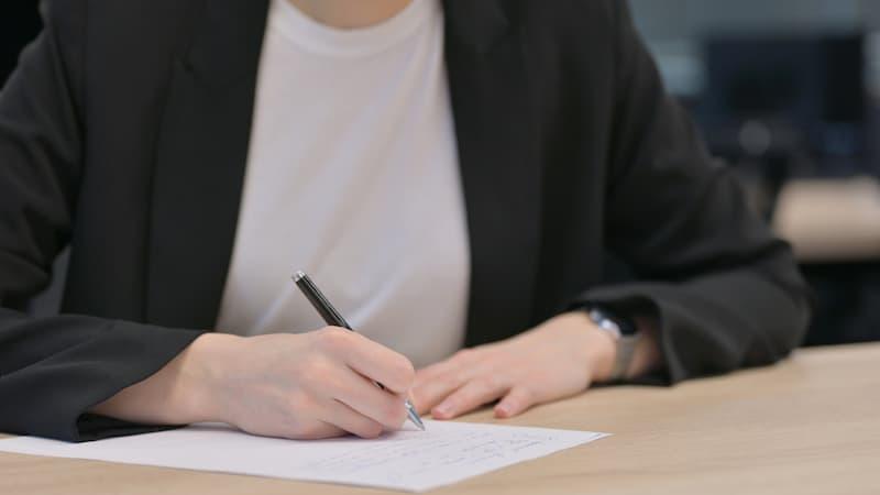 Eine Frau unterschreibt eine Vorkaufsrechtsverzichtserklärung