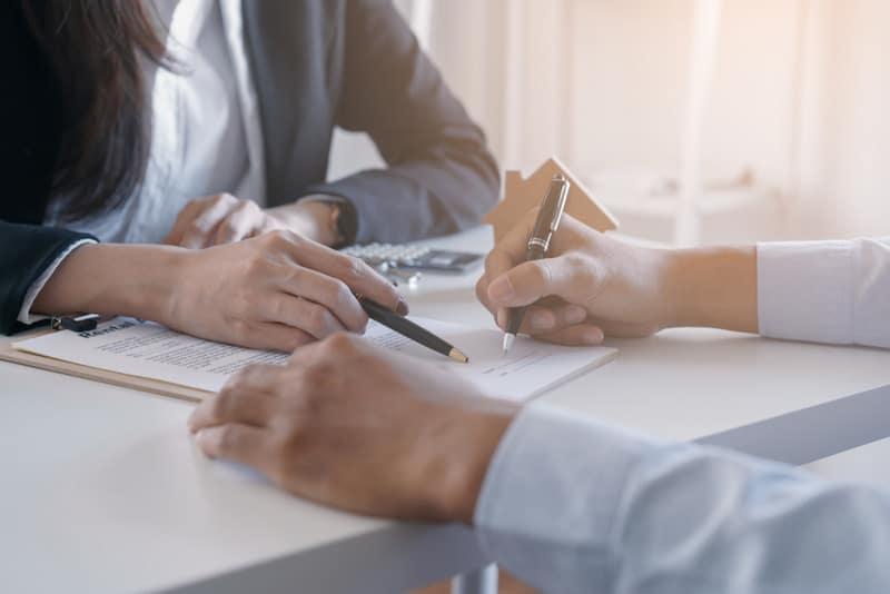 Vermieterin zeigt Mieter, wo er den Mietvertrag unterschreiben muss