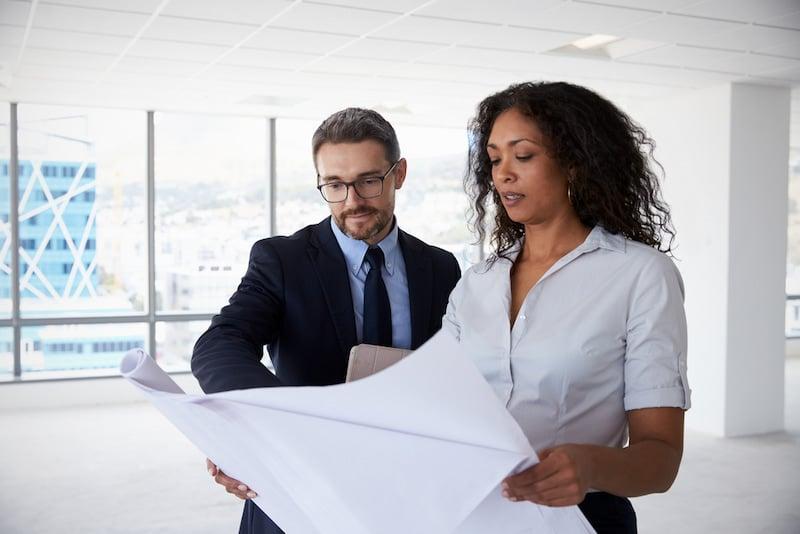 Ein Mann und eine Frau halten einen Plan für die geplante Nutzungsänderung einer Immobilie in den Händen